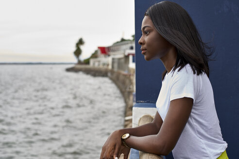 Profile of young woman on terrace looking at the sea - VEGF00073