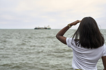 Back view of young woman in front of the sea looking to ship at horizon - VEGF00076