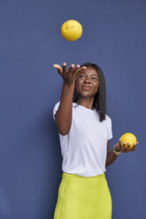 Portrait of happy young woman juggling with two oranges in front of blue background - VEGF00079