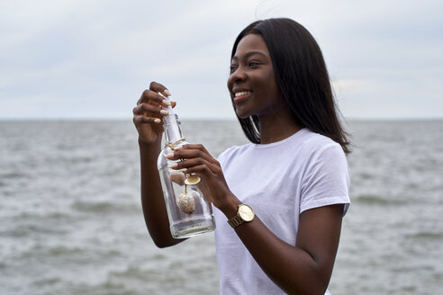 Portrait of smiling young woman in front of the sea sending message in a bottle - VEGF00082