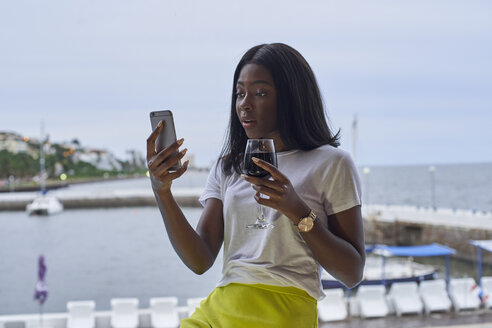 Portrait of astonished young woman on terrace with glass of red wine looking at mobile phone - VEGF00091