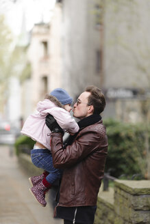 Father holding and kissing his daughter in the city - EYAF00163