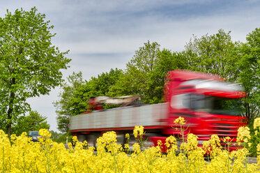 Truck in motion behind rape field - FRF00821