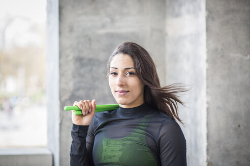 Portrait of smiling young woman holding pound exercise sticks - ASCF00982