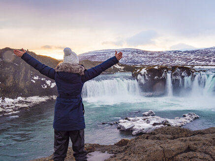 Iceland, woman at Godafoss Waterfall in winter - TAMF01303