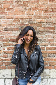 Portrait of young woman wearing black leather jacket, using smartphone, brick wall in the background - MGIF00391