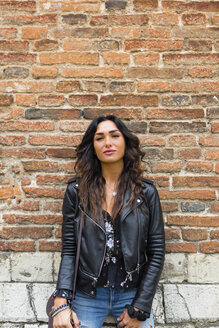Portrait of young woman wearing black leather jacket, brick wall - MGIF00394