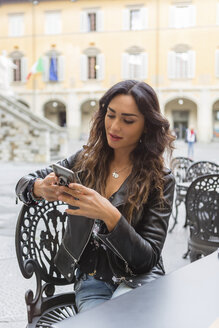 Young woman with cup of coffee, using smartphone - MGIF00397