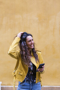 Portrait of young laughing woman wearing yellow leather jacket and holding smartphone - MGIF00403