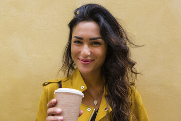 Portrait of young woman wearing yellow leather jacket, holding cup of coffee - MGIF00409