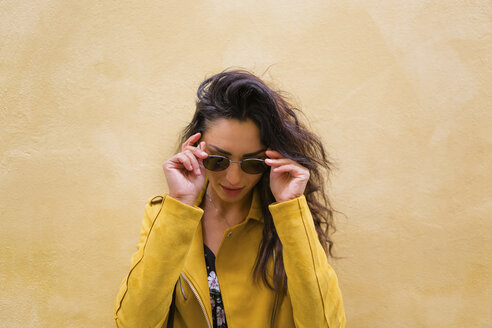 Portrait of young woman wearing yellow leather jacket and sun glasses - MGIF00412