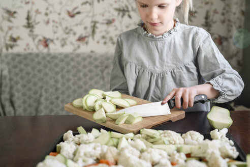 Russia, Moscow, girl slicing vegetables (squash) in sunny kitchen - EYAF00175