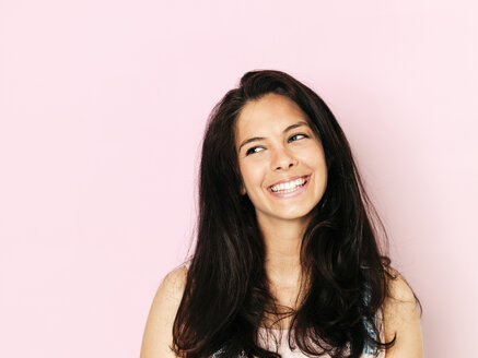 Portrait of young smiling woman with black hair in front of pink background - HMEF00354