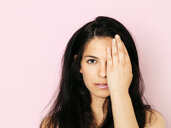 Portrait of young woman with black hair, eye covered in front of pink background - HMEF00357