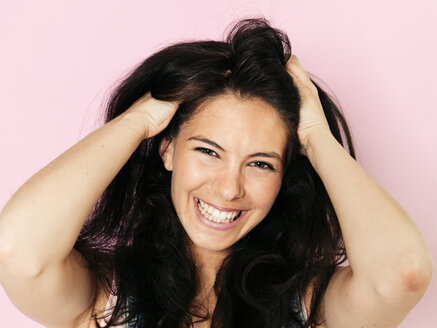 Portrait of young smiling woman with black hair, Hands in hair, in front of pink background - HMEF00363