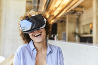 Happy woman wearing VR glasses in modern office - FMKF05624