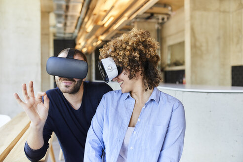Man and woman wearing VR glasses in modern office - FMKF05627