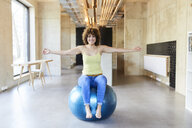 Portrait of smiling woman sitting on fitness ball in modern office - FMKF05648
