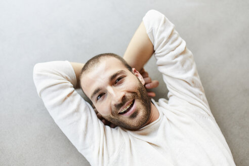 Portrait of happy young man lying on the floor - FMKF05654
