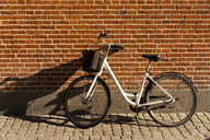 Denmark, Copenhagen, bicycle leaning against brick wall at sunlight - AFVF02729
