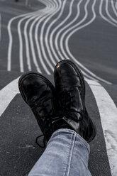 Denmark, Copenhagen, woman's black boots on tarmac - AFVF02738