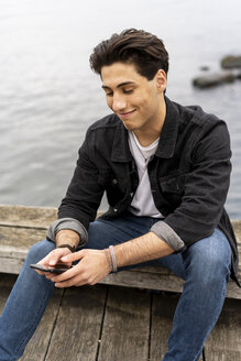 Denmark, Copenhagen, smiling young man sitting at the waterfront using cell phone - AFVF02749