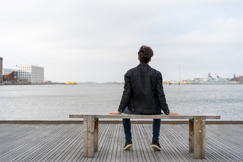 Denmark, Copenhagen, rear view of young man sitting on a bench at the waterfront - AFVF02776