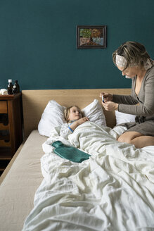 Mother taking temperature of sick daughter lying in bed - PSIF00253