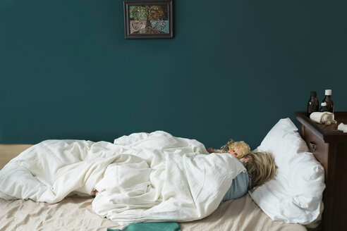 Sick girl lying in bed with doll - PSIF00256