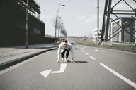 Businessman in starting position on a road with arrow - KMKF00867