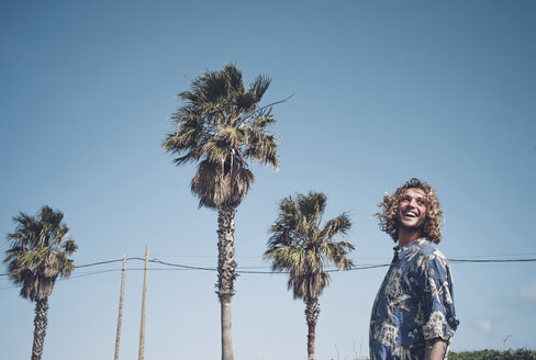 Portrait of laughing blond man posing among palm trees - OCMF00429
