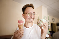 Portrait of young man with ice cream at ice cream parlour - KMKF00870