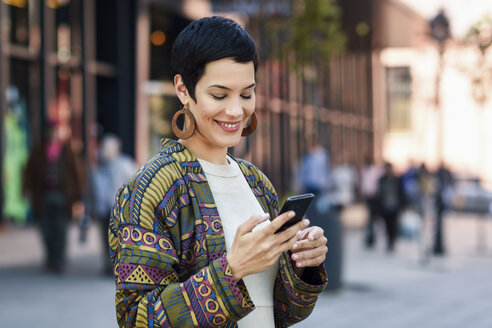 Spain, Madrid, Madrid. Young woman with very short haircut, using smartphone outdoors. Lifestyle concept. - JSMF00966