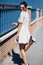 Happy fashionable young woman wearing dress and sunglasses - JSMF00975