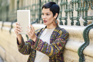 Fashionable young woman using tablet outdoors - JSMF00984