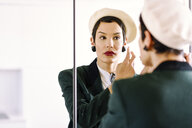 Fashionable young woman checking her look in the mirror - JSMF00987