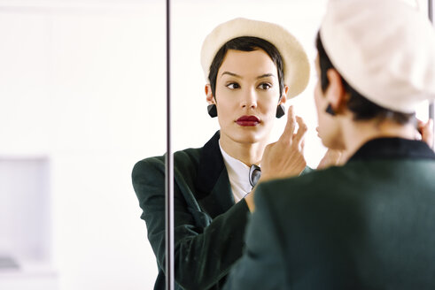 Spain, Madrid, Madrid. Woman with very short hair giving the last touches of makeup in front of the mirror. Lifestyle concept. - JSMF00987