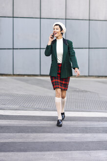 Spain, Madrid, Madrid. Modern woman, wearing green jacket, checked skirt and white beret, using smartphone in the street. Lifestyle concept. - JSMF00993