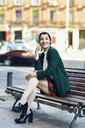 Smiling fashionable young woman sitting on a bench - JSMF00996