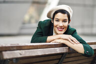Portrait of smiling fashionable young woman sitting on a bench - JSMF00999