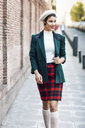 Fashionable young woman walking along a brick wall in the city - JSMF01002