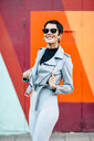 Smiling fashionable young woman with colorful urban background - JSMF01014