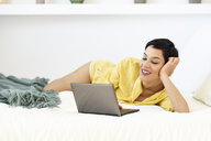 Smiling young woman lying in bed using laptop - JSMF01023