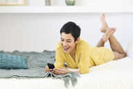 Happy young woman using cell phone in bed - JSMF01029