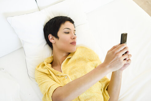 Young woman using cell phone in bed - JSMF01032