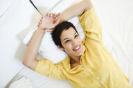 Smiling young woman lying in bed - JSMF01035