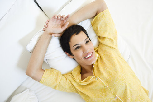 Spain, Madrid, Madrid. Woman with very short hair wearing summer pajamas on her bed. Lifestyle concept. - JSMF01035