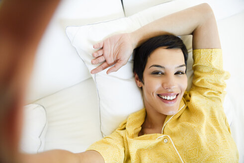 Portrait of smiling young woman lying in bed - JSMF01038