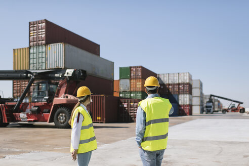 Workers in front of cargo containers on industrial site - AHSF00159