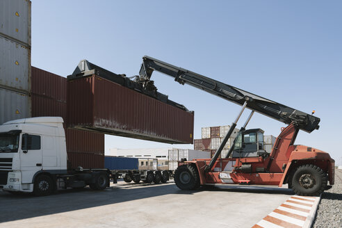 Spain, Aragon, Zaragoza, crane lifting cargo container on truck in logistics company - AHSF00168